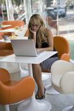 Young woman working with a laptop in a cafe Stock Photo
