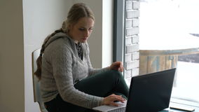 Young woman working on a laptop in a cafe stock video footage