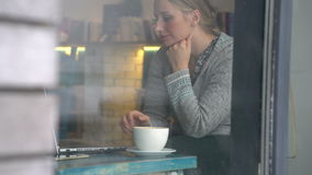 Young woman working on a laptop in a cafe stock footage