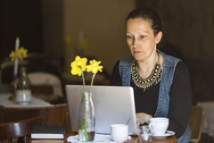 Young woman working with laptop in cafe. Freelanсer. Royalty Free Stock Images