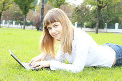 Young woman working on laptop in the city park Royalty Free Stock Photo
