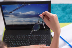 Young woman working on a laptop computer. Holding a pair of eyeglasses in her hand as she surfs the internet, close up view of her hand and the screen of the Royalty Free Stock Photo