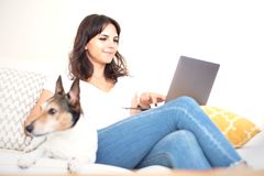 Young woman working on a laptop computer with little dog beside. Attractive young woman relaxing on a sofa with a laptop computer while little Jack Russell lying royalty free stock photos