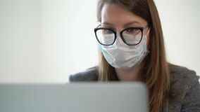 Young woman working at laptop computer in office mask during epidemic covid-19