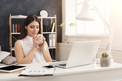 Young woman working on laptop and consulting on phone. Young happy woman sitting at the table, working on laptop, listening music with closed eyes and drinking Stock Image