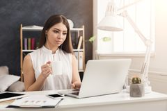 Young woman working on laptop and consulting on phone. Young successful woman sitting at the table, working on laptop, listening music and drinking coffee, copy Stock Photography