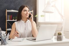 Young woman working on laptop and consulting on phone. Young successful woman sitting at the table, working on laptop and consulting on smartphone, copy space Royalty Free Stock Photography