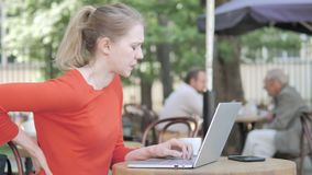 Young Woman Working on Laptop and Drinking Coffee Sitting in Cafe Terrace stock footage