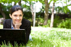 Young woman working on laptop in the field Stock Photography