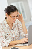 Young woman working on laptop having a headache Stock Image