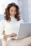 Young woman working on laptop at home Stock Image