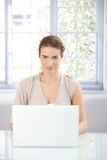 Young woman working on laptop at home smiling. Attractive young woman working at home, using laptop, smiling stock photo