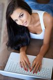 Young woman working on a laptop looking up Royalty Free Stock Images