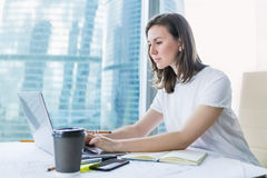 Young woman working on laptop at office Royalty Free Stock Photos