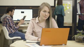 Young woman working on laptop in office stock video
