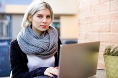 Young Woman Working On Laptop At Outdoor Cafe stock image