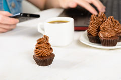 Young woman working with laptop and phone and eating cupcakes wi Stock Image