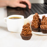 Young woman working with laptop and phone and eating cupcakes wi Stock Photo