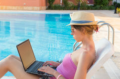 Young woman working on laptop by the pool Royalty Free Stock Image