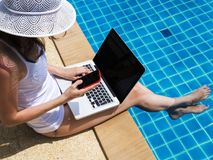 Young woman working on laptop at poolside. Young woman working on laptop computer sitting at poolside with smartphone stock image