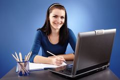 Young woman working with laptop. Portrait of a young woman working with laptop on blue background Stock Photos