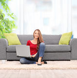 Young woman working on laptop seated on the floor at home Royalty Free Stock Photography