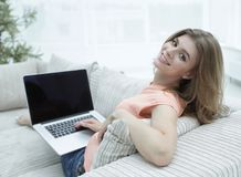 Young woman working with laptop sitting on sofa. And looking at camera.photo with copy space Royalty Free Stock Photo