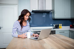 Young woman working on laptop while sitting at table Stock Image
