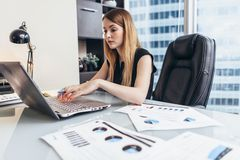 Young woman working on laptop studying financial data and statistics of the company.  royalty free stock image
