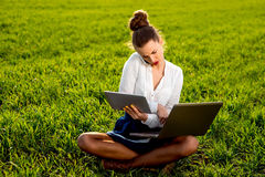 Young woman working with laptop, tablet and phone Royalty Free Stock Photos