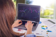 Young woman working on laptop, trading. Blurred background Royalty Free Stock Images