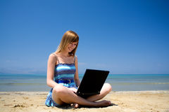Young woman working with laptop on vacation. Young woman smiling on the beach with laptop Royalty Free Stock Photography