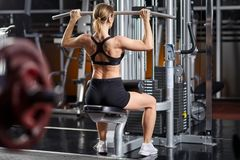 Young woman working the back. Young woman working at the lat pulldown machine in the gym Royalty Free Stock Images