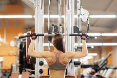 Young woman working at the lat pulldown machine in the gym,. Young woman working at the lat pulldown machine in the gym Royalty Free Stock Photography