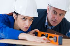 Young woman working with level. Young women working with level woman royalty free stock photos