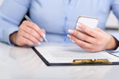 Young woman working with a mobile phone and holding a pen Stock Photos