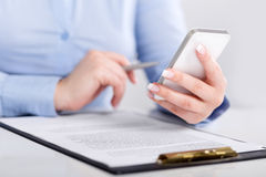 Young woman working with a mobile phone and holding a pen Royalty Free Stock Photos