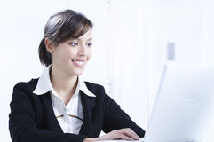 Young woman working in office. With laptop and smiling Royalty Free Stock Image
