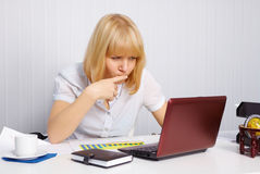 Young woman working in office. Funny young woman working in office with laptop Stock Image