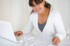 Young woman working at office with a laptop. Portrait of a young woman working at office with a laptop while is looking at you Royalty Free Stock Photo
