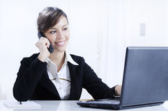 Young woman working in office with telephone stock image