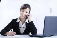 Young woman working in office with telephone Royalty Free Stock Photography