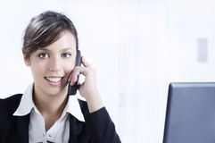 Young woman working in office with telephone. Young woman working in office with laptop and smiling Stock Photography