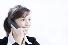 Young woman working in office with telephone. Young woman working in office with laptop and smiling Royalty Free Stock Photography