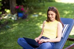 Free Young Woman Working On Laptop In The Garden Stock Photography - 186959332