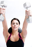 Young woman working out lifting barbells stock images