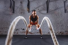 Young woman working out with battle ropes in cross fit gym. Front view of Young woman working out with battle ropes in cross fit gym Royalty Free Stock Image