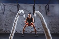 Young woman working out with battle ropes in cross fit gym stock images