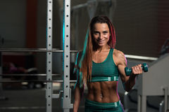 Young Woman Working Out Biceps With Dumbbells Stock Photography