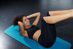Young woman working out at fitness center doing crunch abdominal sit-ups Stock Photos